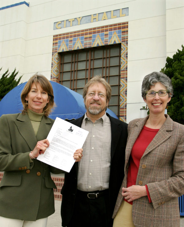 "Santa Monica, CA, January 6, 2004:  (L-R) Shari Davis, Community for Excellent Public Schools (CEPS) co-chair, Ralph Mechur, CEPS committee member, and Louise Jaffe, CEPS co-chair, hold up a copy of the ""Excellent Public Schools Charter Amendment"" which they had just filed at Santa Monica City Hall 1/6/04."